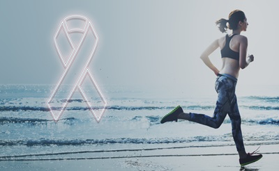 A female breast cancer survivor is running on the beach.