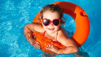 A little girl is wearing sunglasses while using an inner tube in a pool.