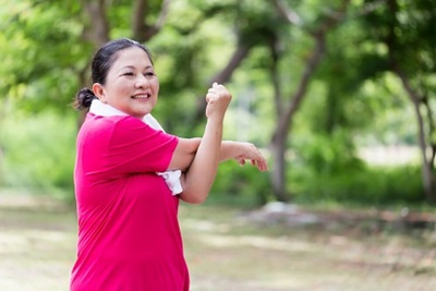 Woman in a pink shirt stretching during her workout