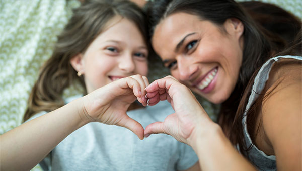 A mother and daughter use their hands to form the shape of a heart.