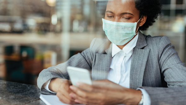 Black businesswoman wearing protective mask on her face while using smart phone and reading text message