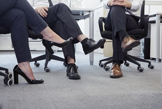 people sitting in office chairs with their legs crossed