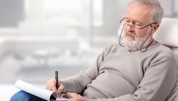 A senior man is taking notes as he studies his Medicare options.