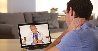 man holding his neck while having a virtual doctor's visit