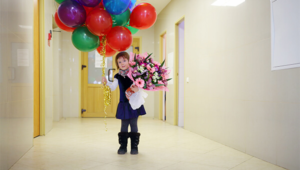 A girl holding balloons and flowers in a hospital hallway