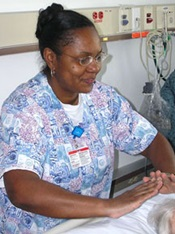 Nurse with purple pattern scrub top spending time with a patient
