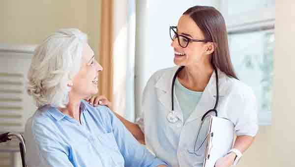 Female healthcare provider talks with senior female patient.