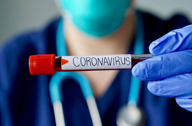 medical professional holding a blood test labeled coronavirus