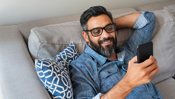Happy smiling latin man using smartphone device while sitting on sofa at home