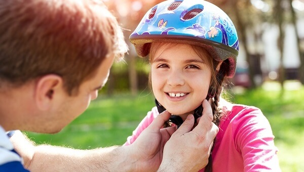 A father is adjusting the helmet on his little girl who is getting ready to ride her bicycle.