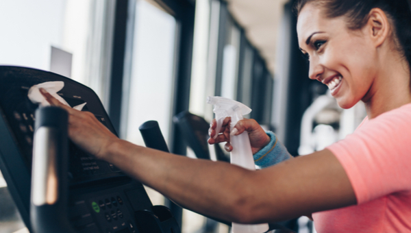 A woman is using disinfectant and a cloth to clean gym equipment.