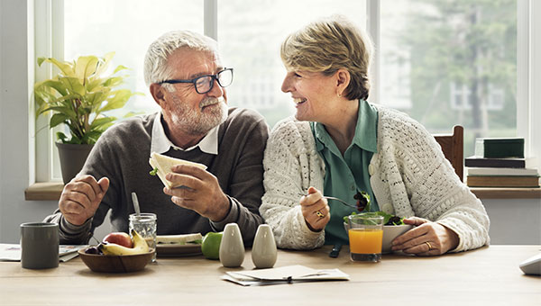 A senior couple smiling while eating breakfast together.