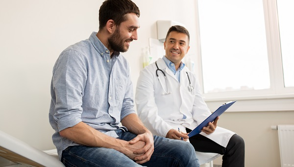 A male doctor is talking with a male patient during an office visit.