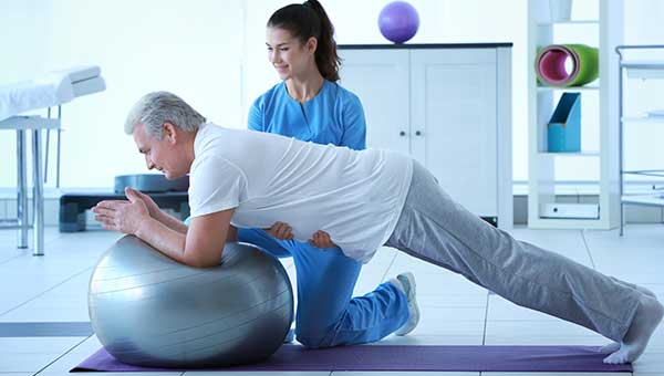 A physical therapist is helping a male patient with rehabilitation exercises.