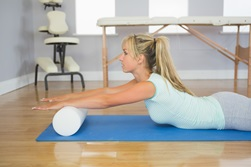 A woman is doing back exercises on a yoga mat.