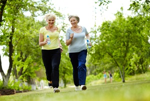 Two senior females are walking in a park.