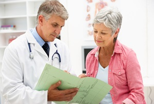 A doctor and a senior woman look over a medical report